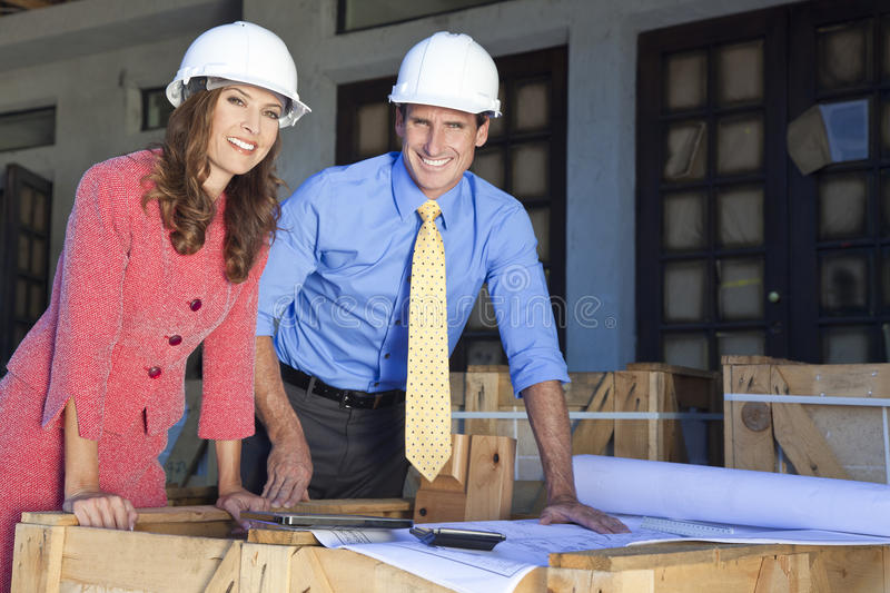 Man & Woman In Hard Hats on Construction Site royalty free stock photography