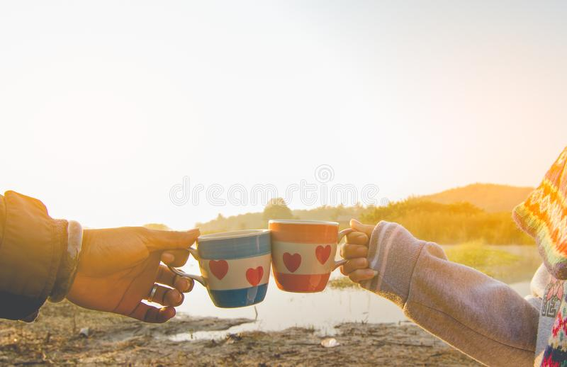 man and woman have a meeting and clinking glasses coffee in nature. stock photo