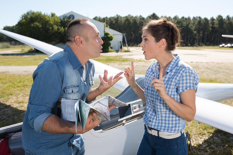 Man and woman having argument in gliding field. Man and women having an argument in the gliding field stock image