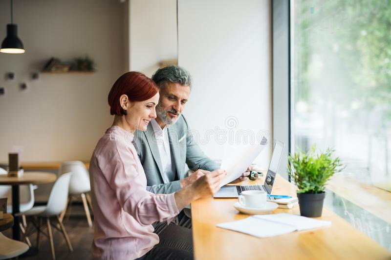 Man and woman having business meeting in a cafe, looking at blueprints. stock images