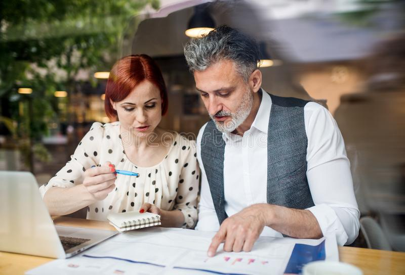 Man and woman having business meeting in a cafe, using smartphone. royalty free stock photo