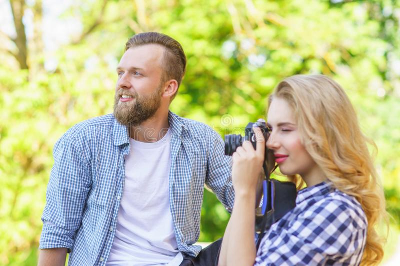 Man and woman having date outdoor. Girl wit a photo camera and her boyfriend. royalty free stock photo