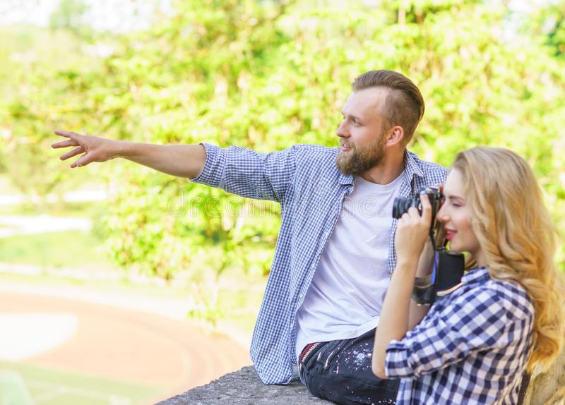 Man and woman having date outdoor. Girl wit a photo camera and her boyfriend. royalty free stock photography