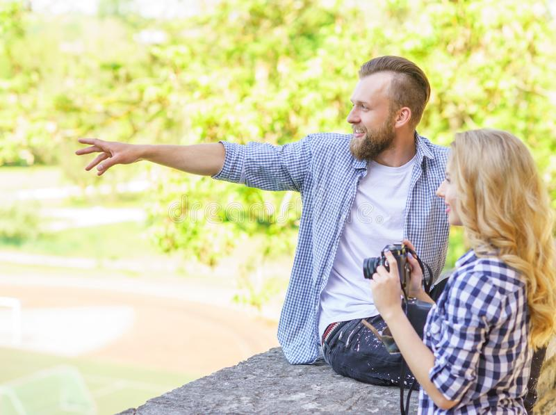 Man and woman having date outdoor. Girl wit a photo camera and her boyfriend. royalty free stock image