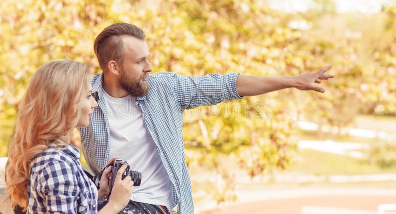 Man and woman having date outdoor. Girl wit a photo camera and her boyfriend. royalty free stock images