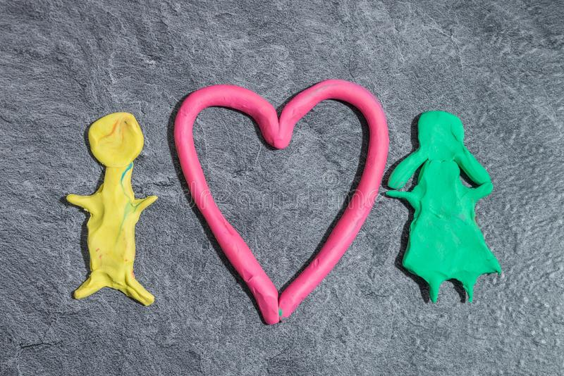 Man and woman with Heart made of play dough in front of grey background.  royalty free stock photo