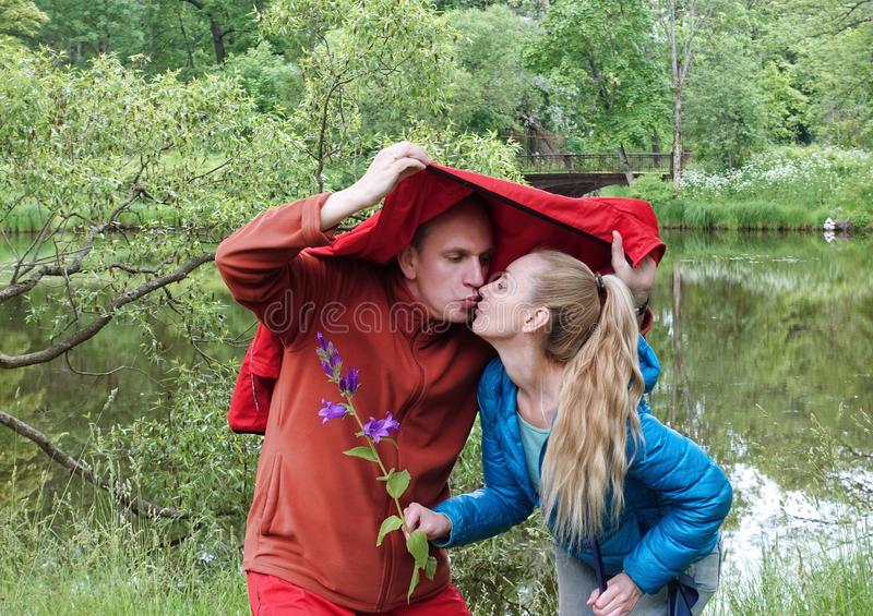 Man and woman are hiding from the rain and kissing on the lake stock images