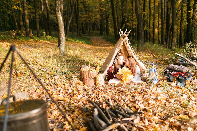 Man and woman hikers camping in autumn nature. Happy young couple backpackers camping in tent. royalty free stock photography