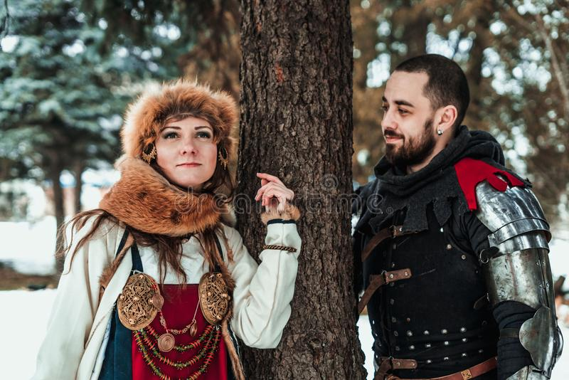 A man and a woman in historical costumes stand near a tree stock photo
