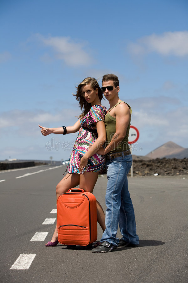 Man and woman hitchhiking. Man and woman on the road hitchhiking under with orange bag royalty free stock image