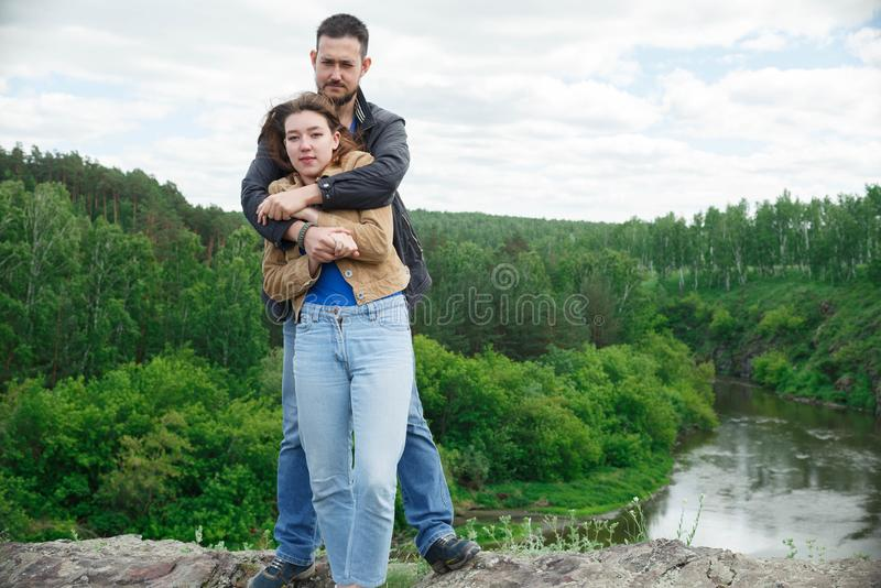 A man and a woman hold each other`s hands on a hill of a mountain royalty free stock images