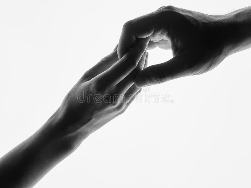 Man woman hold hands silhouette white background. Couple Holding Hands Closeup. Black and white photo. Finger Touching hands silhouette man woman white stock photos