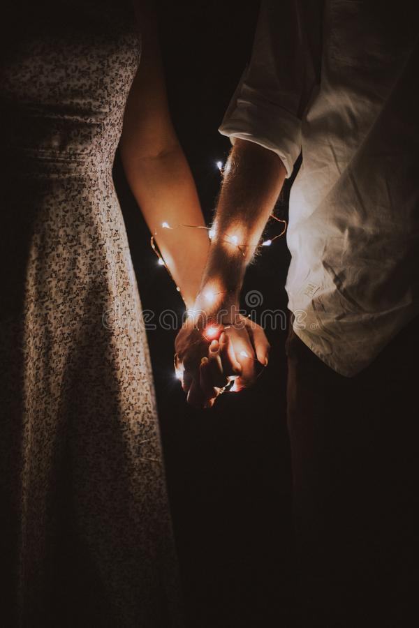 Man and Woman Holding Each Others Hand Wrapped With String Lights stock photography