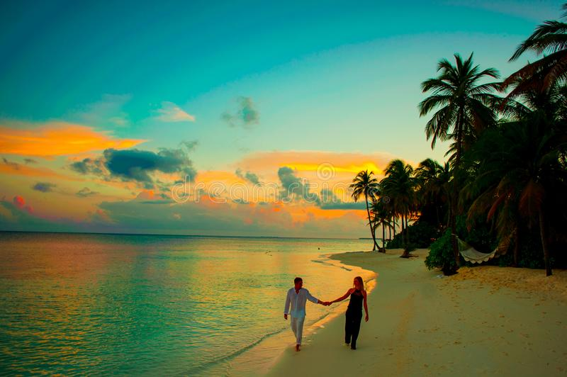 Man and Woman Holding Hand Walking Beside Body of Water during Sunset royalty free stock photography