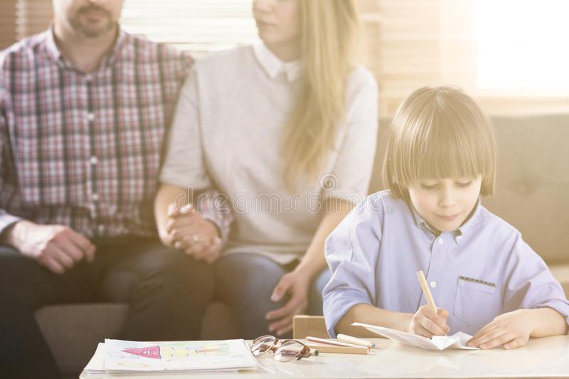 Man and woman holding hands on a couch and a boy in front drawing pictures by a table during a family psychotherapy session. stock photos