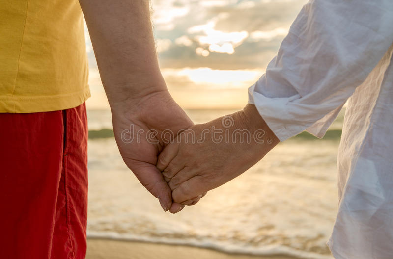 Man and woman holding hands stock image