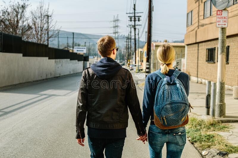 Man and Woman Holding Hands While Walking stock image