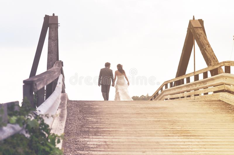Man and Woman Holding Hands While Walking on Bridge stock images
