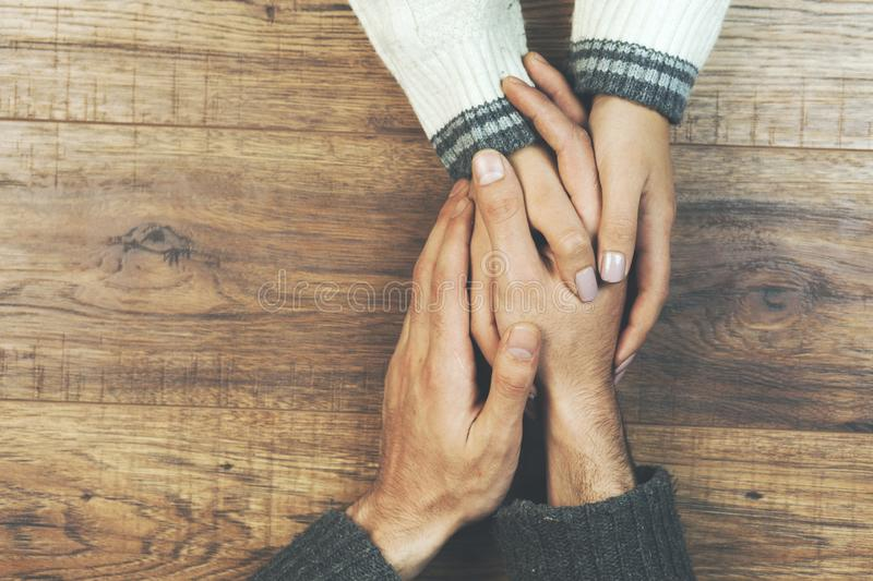Man and a woman holding hands at a wooden table.  royalty free stock photography
