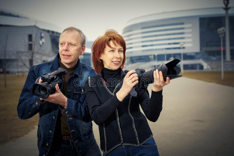 A man and a woman are holding photos and video cameras in their hands stock photos