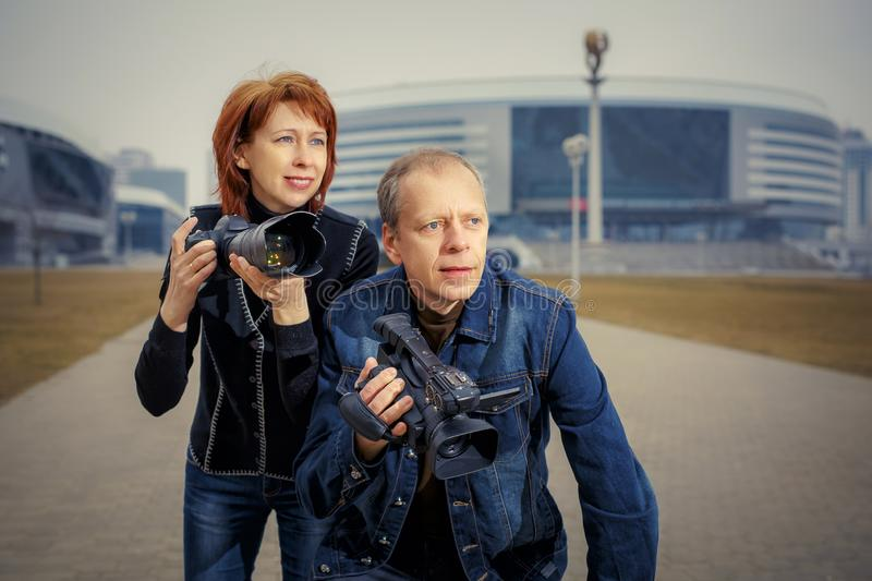 A man and a woman are holding photos and video cameras in their hands royalty free stock image