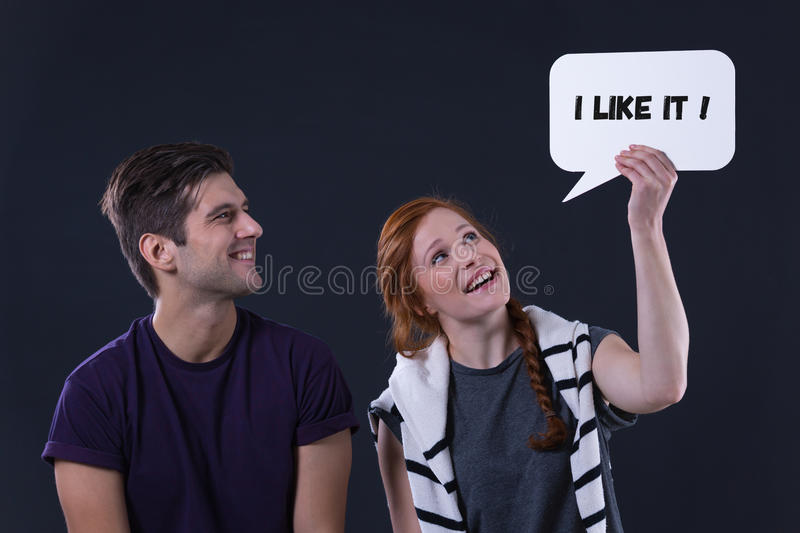 Man and woman holding speech bubble `i like it`. Happy men and women holding speech bubble `i like it royalty free stock images