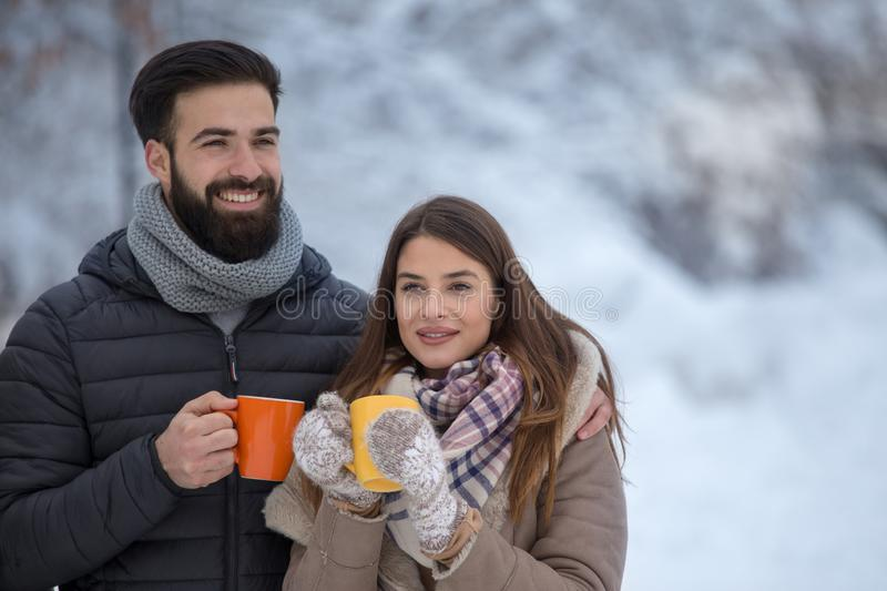 Man and woman with hot drink on snow. Young couple holding cup of hot drink on snow in forest royalty free stock photos