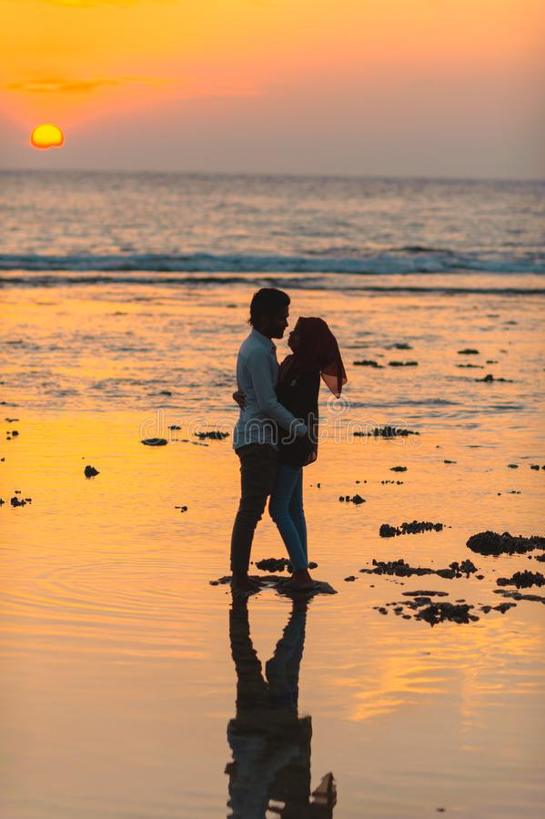 Man and Woman Hugging by the Seashore during Sunset stock photography