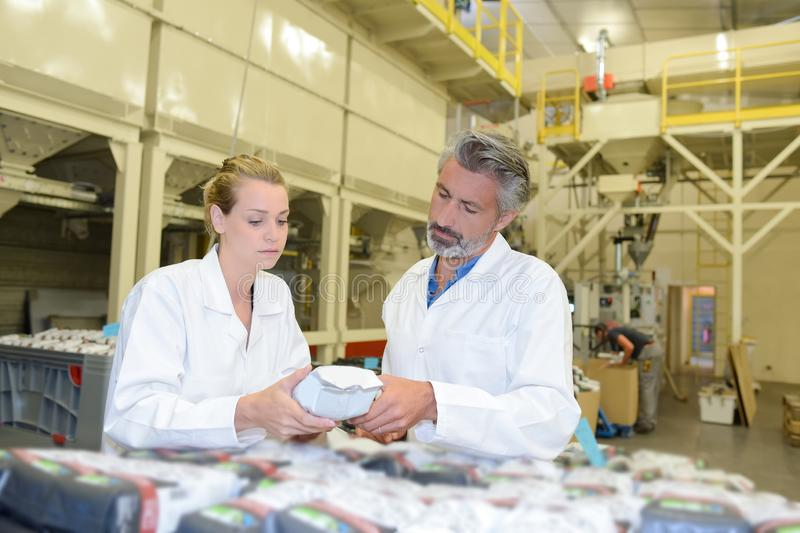 Man and woman inspecting sealed packet. Man and women inspecting sealed packet inspect royalty free stock photos