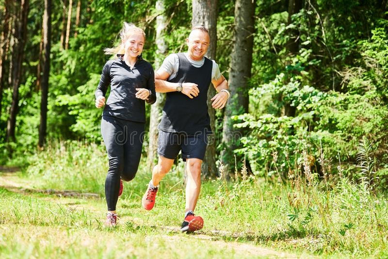 Man and woman jogging and running outdoors in forest stock photos