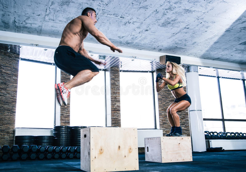 Man and woman jumping on fit box. Man and women jumping on fit box at gym royalty free stock photos