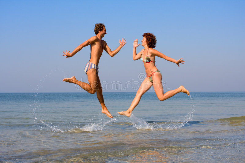 Download Man And Woman Jumping In Sea Stock Photo - Image: 6171632