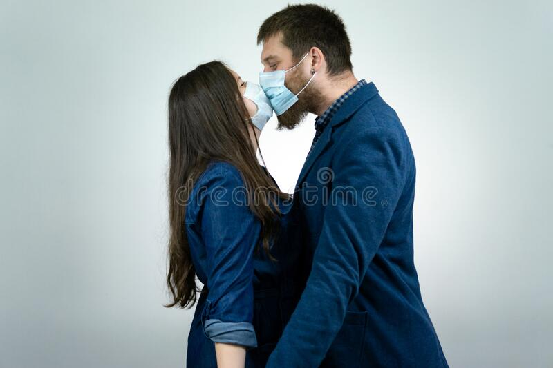 Man and woman kisses each other at protected face mask, protection against the virus. Pandemic. Coronavirus.  stock photo