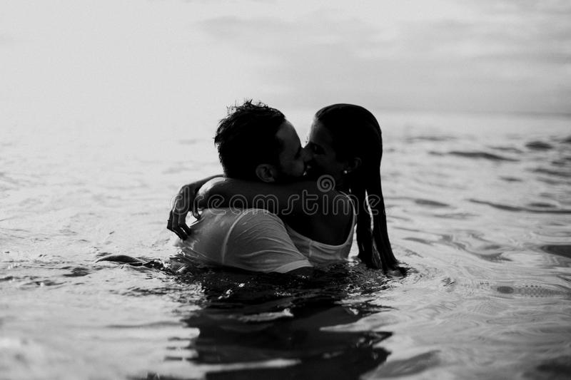 Man and Woman Kissing Together on Body of Water stock image