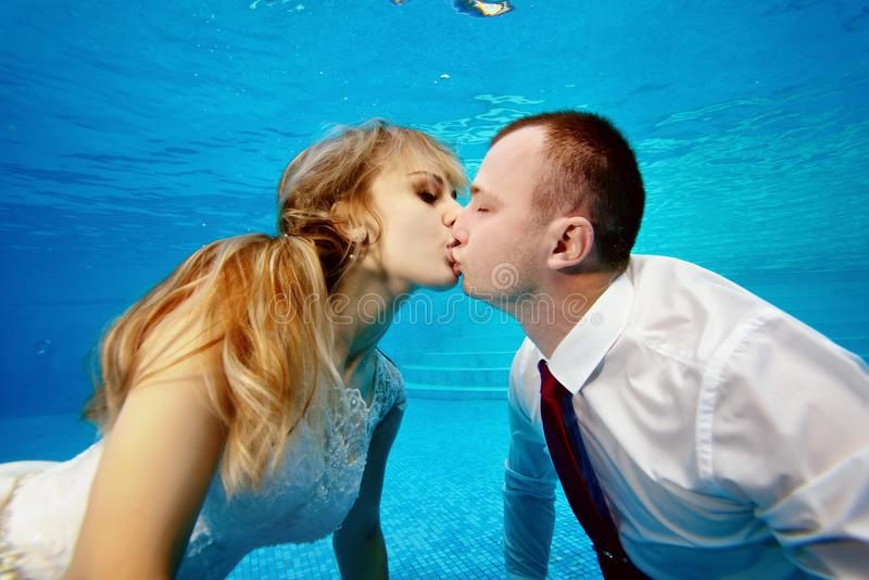 Man and woman kissing underwater in the swimming pool stock photography