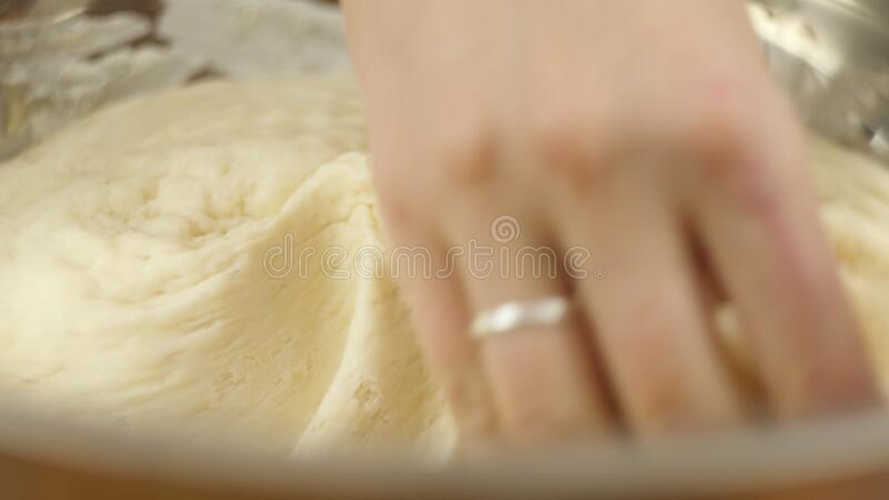A man or woman knead the yeast dough in a bowl with his hands. Home bakery. Private business. Man or woman knead the yeast dough in a bowl with his hands. Home stock photography