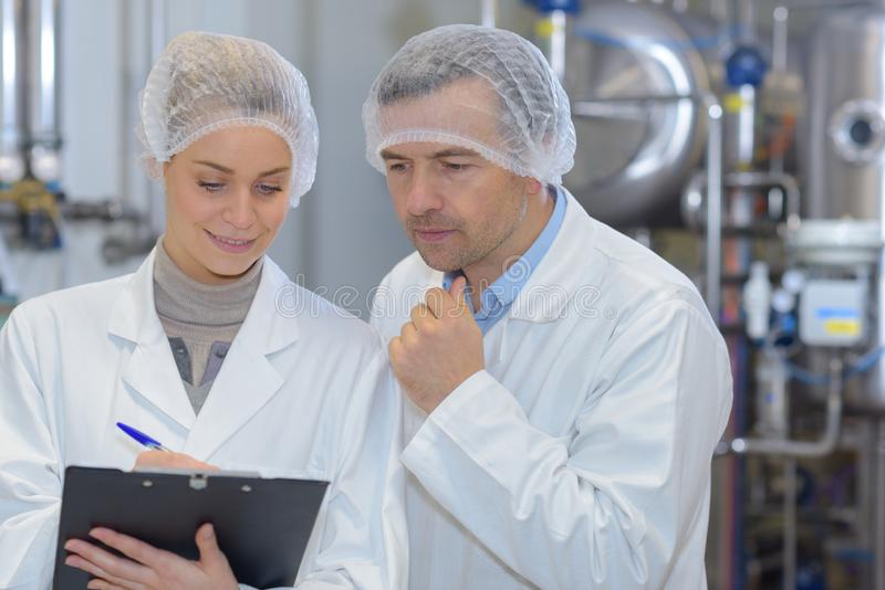 Man and woman in lab coats working in factory stock images