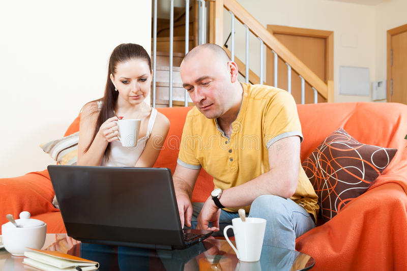 Man and woman at laptop at coffee table stock image