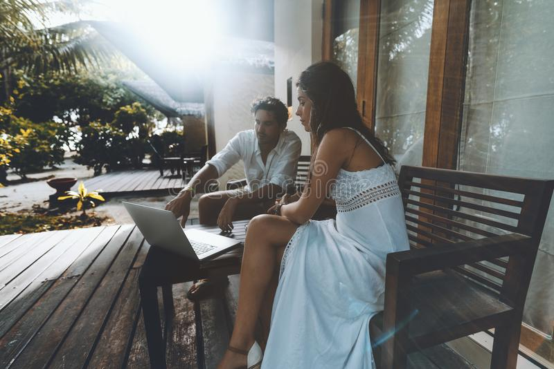 Man and woman with laptop near their summer house. Charming women in is sitting outdoors with her husband on the wooden chairs near their summer house and stock photos