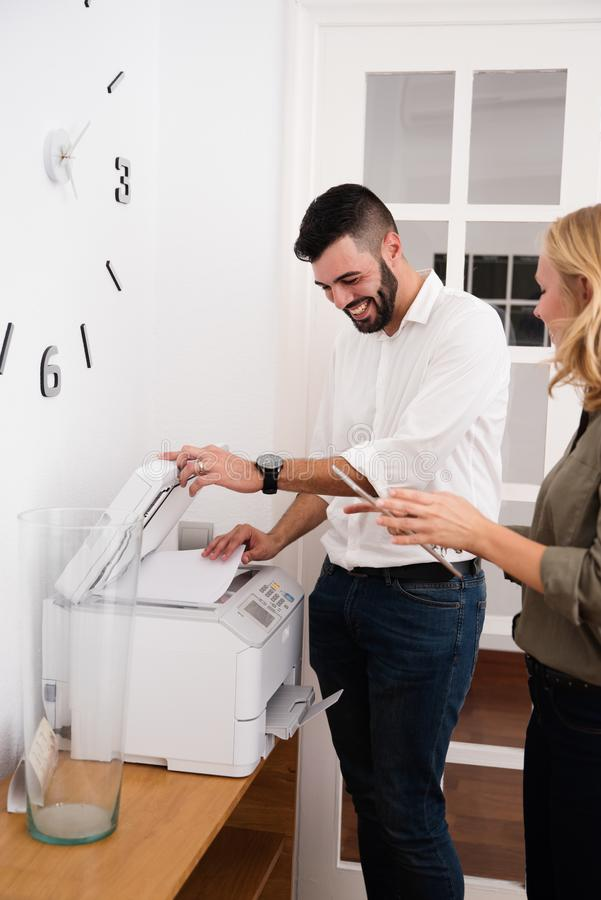 Man and woman laughing over a photo copier stock photos