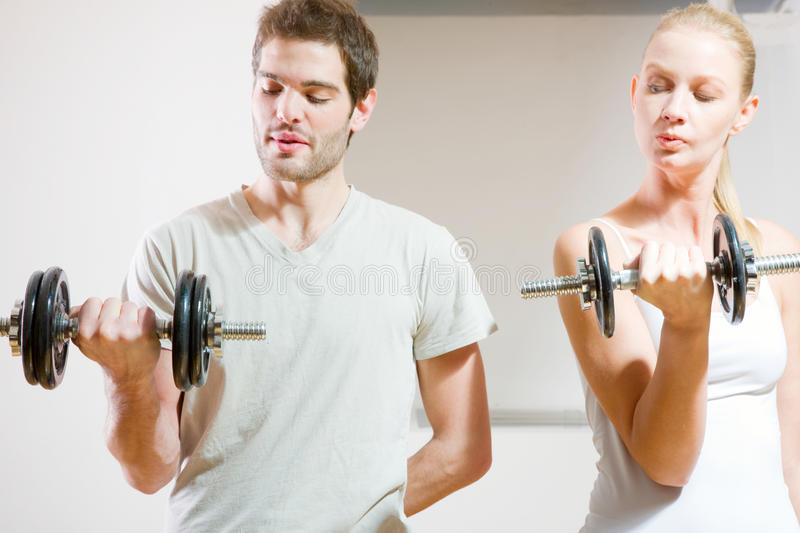 Man and woman lifting dumbbell stock photo