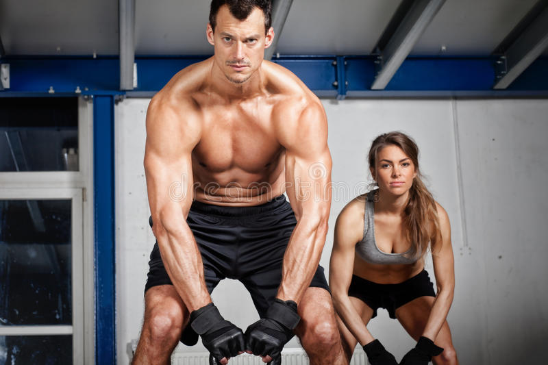 Man and woman lifting kettle bell crossfit. Man and women lifting kettle bell crossfit in a gym stock photo