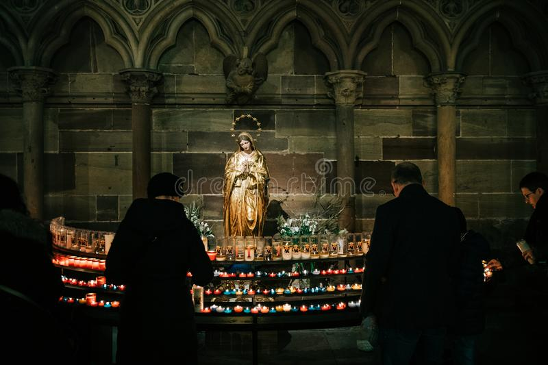 Man and woman light candles in Cathedral Notre-Dame with mary St stock image