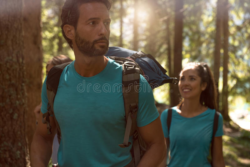 Man and woman looking around while walking along hiking trail path in forest woods.Group of friends people summer stock images