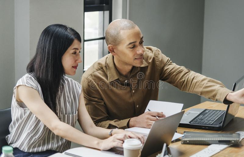 Man and Woman Looking at Laptop Computers royalty free stock images
