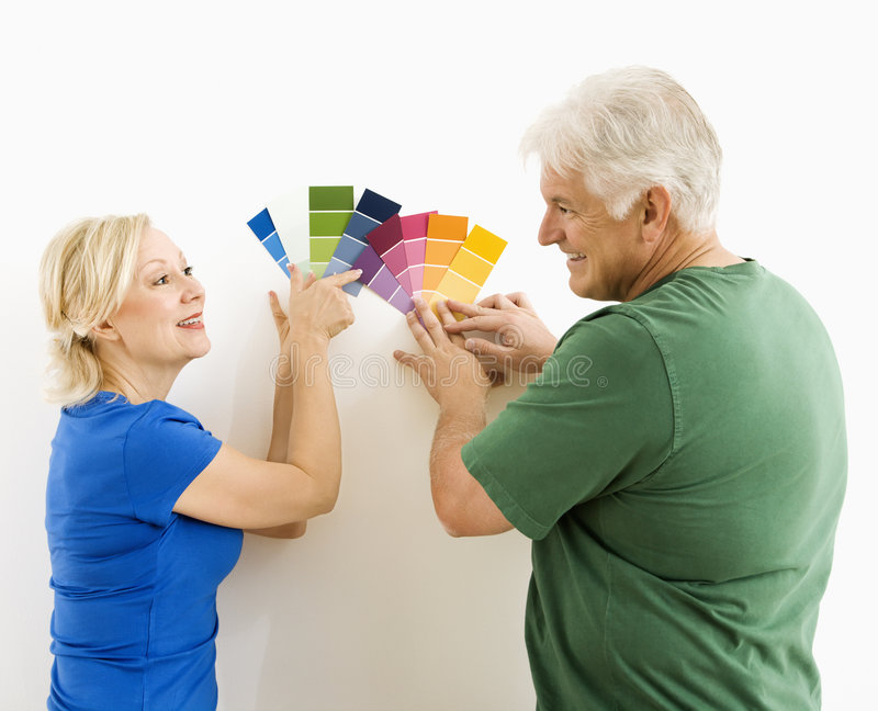 Man and woman looking at swatches. Middle-aged couple comparing and discussing paint swatches royalty free stock image