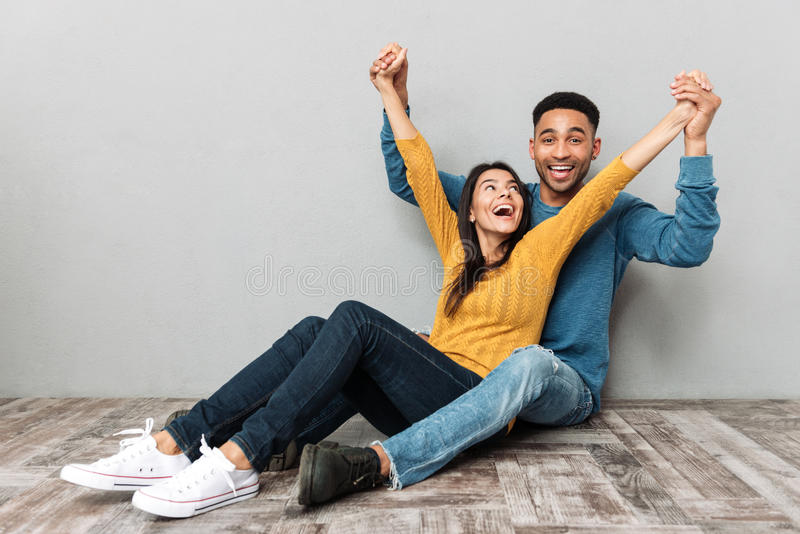 Man and woman in love having fun. Full-length shot of african cheerful men and happy women in love having fun sitting on floor isolated stock photography