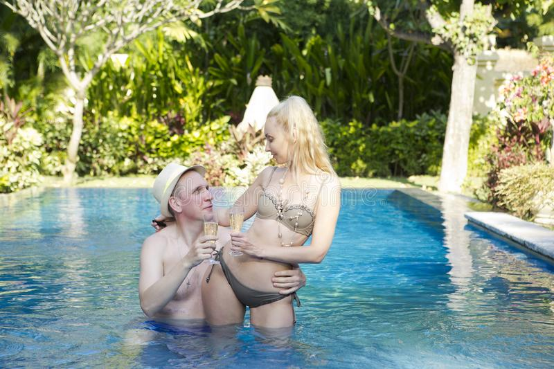 Man and woman, loving couple, in pool in a garden with tropical trees hold glasses with wine in hand stock images