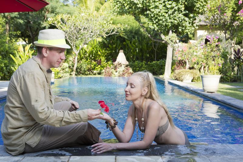 Man and woman, loving couple, in pool in a garden with tropical trees stock images