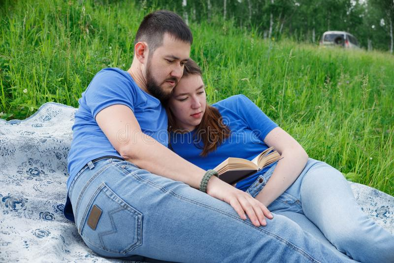 A man and a woman are lying on the grass and reading a book royalty free stock image